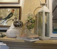 Summer mantel with trumeau mirror, flanked by lanterns, books, glass apothecary jars filled with greenery, more glass, silver balls and lacy ceramic.