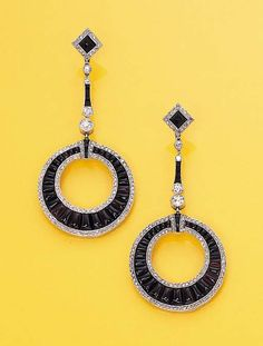 A PAIR OF DIAMOND AND ONYX EAR-PENDANTS   Each designed as a calibré-cut onyx tapered hoop with rose-cut diamond borders to the onyx and diamond-line surmount and top, circa 1922