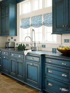 Cabinets are a practical necessity in a kitchen, but they can also be a useful design tool in establishing an aesthetic. Take this space: An aged glaze and rich color transform a newly built area into one with an always-been-there feel. Because it's already a distinctive color, the blue appears just here and there, in tiles on the backsplash and in the Roman shades. Neutral-color tiles underfoot provide a warm contrast.