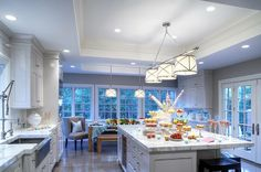 Honey We're Home's blog has a great section on white kitchen inspiration ideas for the author's own white kitchen. Love the lighting and the apron front sink as well as the coloring of the hardwood floors.