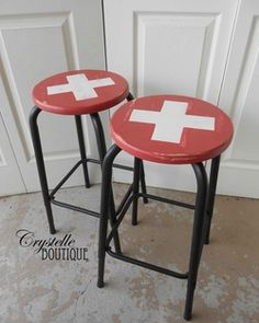 Vintage Stools: black metal legs, Wooden seats with flag of Switzerland in paint. Red and white cross Crystelle Boutique