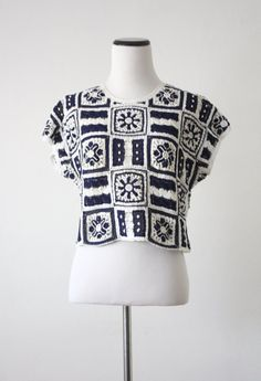 Vintage 1970s crochet top in navy blue and white with an accent of tiny pearly beads. Pullover with two buttons at the back of the neck. Will best