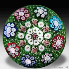 "Parabelle Glass 1992 concentric millefiori on moss ground paperweight. A central Clichy-type pink and green rose cane is encircled by a ring of alternating pink/green and white/green Clichy-type roses. A multi-colored collection of spaced complex millefiori encircles the piece, on a bright green moss ground studded with tiny white edelweiss canes. Signature/date cane on the underside. Diameter 2 3/4"". www.theglassgallery.com"