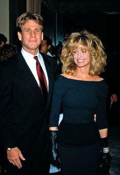 Farrah smiles with actor Ryan O'Neal, 1987.