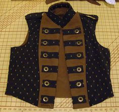 This is a bespoke man's reversible double-breasted vest.  One side is brown cotton canvas, and the other side is black and brown silk brocade.  This photo shows the brocade side out, with the front open and the double-breast folded back.