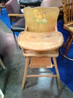 This vintage wooden high chair has a petite frame and an old-fashioned wood design. In addition, the back of the high chair has a lovely baby drawing.