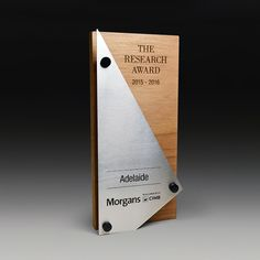 Morgans CIMB Research Award as Stainess and Plywood Trophies | Master Engraving. Recognising excellence in research and performance, the Morgans CIMB design incorporates both these qualities with its material selection. The deeply laser etched thick plywood timber provides high environmental credentials using low carbon footprint plywood while the stainless steel face suspended with black standoffs offer a high performance contrast to the timber.