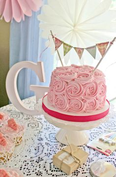 My baby girl's shabby chic 1st birthday party at her Grammy & Papa's :) I made the cake bunting with shabby chic scrapbook paper, cut into triangles. I ran a thin string through tiny holes punched at the top of the paper. Then tied the ends to lollipop sticks. I also made a matching pennant banner for behind the table!