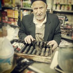 Iranian store owner with his chortekeh. (Abacus)