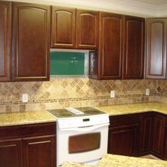 gold St Cecilia Granite countertops with tile backsplash and white gas stove