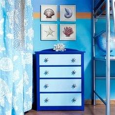 An old white dresser was repainted with two shades of blue to add a modern touch. Starfish knobs tie in the ocean theme and coordinate with lithographs of sea life hanging above the dresser. A stripe on the wall painted in a contrasting orange adds a simple dash of style.   Editor's Tip: Purchase inexpensive knobs with sports or other fun themes at Target and replace the bland hardware on your child's dresser drawers.