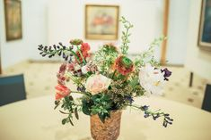 """Mayumi used roses, ranunculus, parrot tulips, and peonies to create stunning centerpieces for the Bruno Zupan """"What I See"""" art exhibition show. Mayumi used Zupan's paintings as inspiration for the designs."""