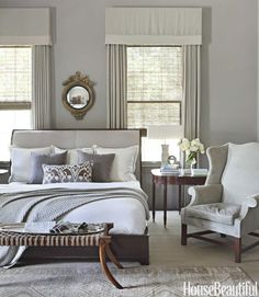 """To make the master bedroom of this Alabama home more dynamic, designer Betsy Brown choose bright white bedding and a white lampshade. """"A room of creams and beiges needs something stark and shiny white. You have to interject elements that add intense personality,"""" says Brown. Walls are Rockport Gray by Benjamin Moore. Saber Leg ottoman by Formations. Cashmere blanket from Suite Dreams. See more ways to decorate with color.   - HouseBeautiful.com"""
