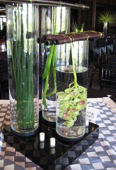 """Floating"" green cymbidium orchids and green equisetum under water in large clear glass cylinders."