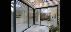 This rear kitchen dining, living extension in South West London benefits from IQ's large sliding glass doors to the rea. The impressive floor to ceiling sliding glass doors are designed...