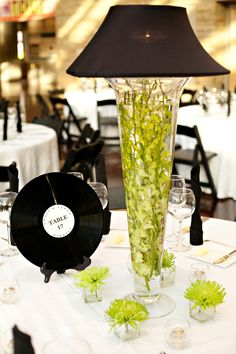 Tall vase filled with flowers topped with a lampshade  Record table numbers