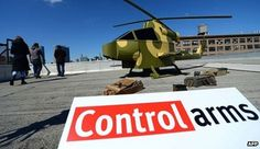 Activists put a replica of a military helicopter on a roof near the UN in New YorkThe UN General Assembly has passed the first global arms trade treaty by 154 votes to three, with 23 abstentions.Iran, North Korea and Syria had sought to block the treaty governing a trade worth some $70bn (£46bn)