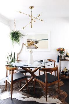 Dining Room decor ideas - small modern eclectic bohemian style dining with round glass topped table, sputnik light fixture, wood and leather chairs, rawhide rug and pops of greenery.