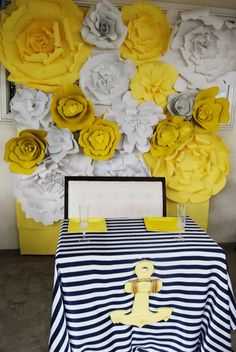 Paper flower wall. Parents to be eating table. Nautical baby girl shower! Yellow, Navy blue and white.