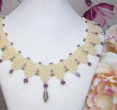 This lace bead weaving necklace is made with pearl seed beads, accents of violet opal Swarovski crystals and olive pressed glass, fluorite drop pendant. Description from zeesi.com. I searched for this on bing.com/images