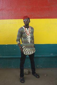 Một chàng trai người Ghana trong bức ảnh của Ed Suter. Phía sau nền của bức ảnh là lá cờ của Ghana với 3 màu sắc. Chàng trai ăn vận sành điệu với sự phối hợp màu sắc rất thời trang