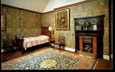 """""""Honeysuckle"""" (1876) wall hangings designed by May Morris, daughter of William Morris. The room holds 2 Morris & Co. """"Sussex Chairs"""", an armchair & corner chair (at foot of the bed). A """"Small Barr"""" Hammersmith (carpet) designed by William Morris, graces the floor at Wightwick Manor, Wolverhampton, West Midlands."""