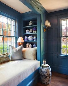 Stunning blue paneled library features a white and blue drum stool placed in front of a blue built-in window seat topped with an off-white seat cushion flanked by built-in shelves housing white and blue chinoiserie vases. Built In Bookcase, Blue Bookshelves, Built In Daybed, Built In Seating, Cozy Nook, Bed Nook, Building For Kids, Trendy Home, Built Ins