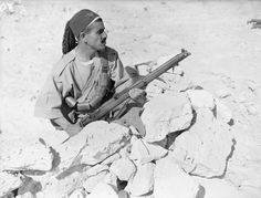 ARAB LEGION NORTH AFRICA (E 86)   An Arab Legion rifleman armed with a SMLE (Short Magazine Lee-Enfield) Mk III shelters behind rocks, Mersa Matruh, Egypt, 28 May 1940.