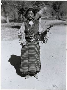 Photographer: Frederick Spencer Chapman, Collection: Hugh E. Richardson, Date of Photo: November 10th – 12th 1936, Region: Lhasa,Dekyi Lingka in November 1936. She is wearing a brocade outer garment and has an elaborate charm box or gau at her neck.