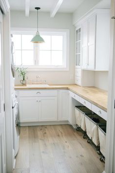 Beautiful laundry room with stackable front load washer and dryer across from three No.185 Square ...