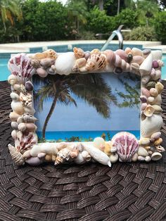 Real sea shells create a stunning 1 inch boarder on this 8X6 wooden picture frame. Frame is handcrafted. Each shell was meticulously placed to craft a beautiful work of art. This is the perfect frame to hold memories from the ocean or your perfect vacation. Frame holds a 4X6 picture.