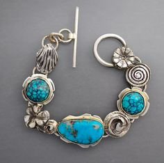 A lovely sterling silver bracelet with three natural turquoise cabochons and wonderful hand fabricated silver elements. Seven and one-quarter inches in