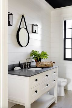 Modern farmhouse bathroom with shiplap walls, white vanity, black counter and natural fiber accents.