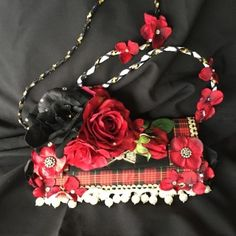 A stylish clutch in black and red roses on a tartar pattern trimmed with pearls. A bold approach to a traditional pattern. Looks fantastic with black dress. Silk flowers adorn the black and white strap.