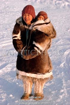 Image of leah, an inuit woman, carries her baby in an amaut (hooded parka) on her back. igloolik, nunavut, canada. by ArcticPhoto