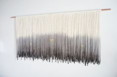 Each piece of cream colored yarn is individually hand cut and strung on the copper rod, then carefully dip-dyed to create a one-of-a-kind tapestry. From the dye saturation to the way the fibers fall organically, no two wall hangings are the same making this a unique and beautiful statement piece for your home. The ombre tapestry is a blend of grey and black dye, complete with gold accent beading. The copper rod is 60 wide. The length is approximately 30. The tapestry can be hung simply by…