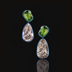 SPECTACULAR PAIR OF PERIDOT AND FANCY YELLOW-BROWN DIAMOND PENDANT EAR CLIPS, TAFFIN Each surmount set with an oval peridot suspending a fancy yellow-brown pear-shaped rose-cut diamond weighing respectively 28.75 and 31.51 carats, to a blue titanium border, mounted in yellow gold