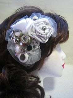 This beautiful and one-of-a-kind bridal hair comb is perfect for the modern bride who wants to wear a headpiece but forgo a veil. Satin handmade ribbon roses in shades of white, and grey silver have been affixed to a felt backing. They have been further embellished with vintage buttons, faux rhinestones, and white tulle for a stunning result. A hair comb has been stitched to the felt backing.