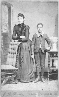 Unidentified standing figures: woman, her folded arms leaning on back of chair, and young man, probably her son, left hand on book.  Savannah, Georgia 1890.