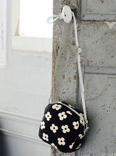 モノトーンの花柄のテキスタイルが生きる、シンプルなファスナー使いのポシェット。 ショルダー持ち手がレザーなので、きちんと感があります。