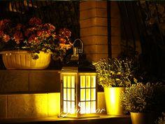 Lanterns at night in a charming garden. Lampion drewniany w białym kolorze z metalowych błyszczącym daszkiem. Lampion na schodach, na tarasie nocą.