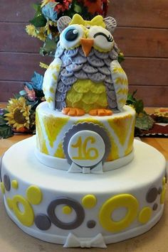 A sweet 16 owl cake with yellow and grey details and a hand painted chevron pattern! The cake is a chocolate fudge cake filled with chocolate swiss meringue butter cream and iced in a dark chocolate ganache before covering it in marshmallow fondant