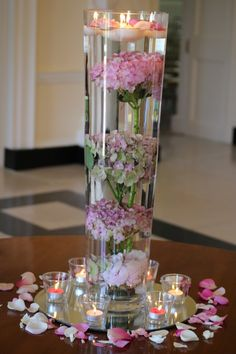 unusual floating candles tall vase centrepiece with submerged hydrangeas, surrounded by petal scatter and votives. From wedding at Botleys Mansion. Entrance hallway at Botleys Mansion.