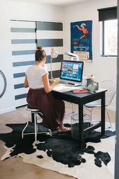 escritorio super cool com tapete de vaquinha, poster de pin up e luminária vintage