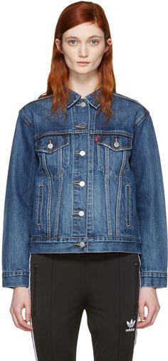 Long sleeve denim jacket in 'groovemarks' blue. Fading, distressing, and discoloration throughout. Spread collar. Button closure at front. Flap pockets at bust featuring logo flag in red. Welt pockets at waist. Single-button barrel cuffs. Adjustable buttoned cinch tabs at back hem. Contrast stitching in tan.