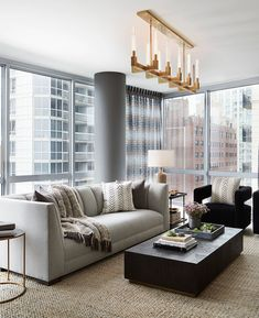 Elegant grey living room decor in Chicago loft with restoration hardware style swivel armchairs and channel tufted sofa #rh #restorationhardware