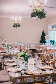 Elegant wedding reception idea - green + white floral centerpieces and greenery on chandelier {Woodland Fields Photography}