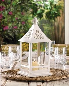 A twist on the traditional candle lantern, the Belfort features a metal lantern frame that harbors a round glass candle cup. The metal structure is painted white and has a top loop for hanging. The roof features beautiful floral-inspired cutouts. Table Lanterns, Lantern Centerpiece Wedding, White Lanterns, Wedding Lanterns, Candle Centerpieces, Wedding Table Centerpieces, Centerpiece Decorations, Decoration Table, Wedding Decor