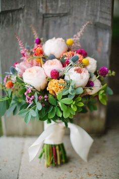 A bouquet of purple wax flowers, peach English garden roses and yellow coxcomb