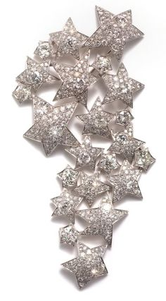 """Platinum and diamond-set """"22 stars"""" brooch by Suzanne Belperron, in the form of an articulated trail of twenty-two stars of varying size, set with brilliant cut diamonds Paris, circa 1935"""